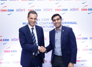 Rodolphe Saade and Karan Adani shake hands after signing the Munda CT4 deal