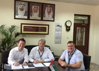 Captain Cliff Brand (centre) signs the deal to buy two Liebherr mobile harbour cranes
