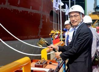 Takaaki Anraku, President, Kokusai Cable Ship Company, cutting the rope to break the milk pot against the vessel's hull