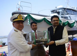 Rear Admiral Syed Hasan Nasir Shah, Managing Director of KS&EW, with an employee holding the ship's model and Dr Miftah Ismail, Advisor to the Prime Minister on Finance, Revenue & Economic Affairs