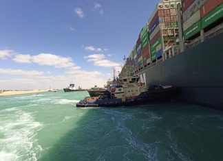Tugs working to free the stricken container ship in the Suez Canal