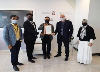 Robert Sutton, Head of Logistics Cluster, AD Ports Group, receiving the GDP Accreditation Certificate from Bureau Veritas' representative in the presence of a number of the Group's officials.